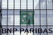 An employee walks behind the logo of BNP Paribas in a company's building in Issy-les-Moulineaux, near Paris, June 2, 2014.
