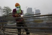 A labourer, wearing an improvised protective mask, welds steel bars at a residential construction site in Quzhou, Zhejiang province April 3, 2014.