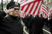 New York City police officer Brian Lukowsky salutes New York City firefighters as they march in the annual St. Patricks Day parade