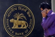 A man makes a phone call while standing near a Reserve Bank of India (RBI) crest at the RBI headquarters in Mumbai January 29, 2013.