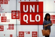 A woman checks her phone in front of a panel outside the flagship store of Japanese fashion house Uniqlo at Hong Kong's Causeway Bay shopping district May 9, 2013.  Credit: REUTERS/Bobby Yip