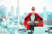 Businesswoman wearing cape and mask in office