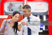 Smiling salesman showing woman cell phone in electronics store