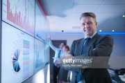Company manager in front of graphs on screen in meeting room, portrait