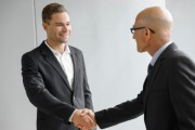 Senior and young businessman shaking hands