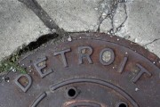 'Detroit' is seen on the top of an iron man-hole cover on a street in Detroit, Michigan July 27, 2013.