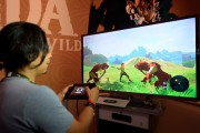 Gamers try out the new to play the new video game 'The Legend of Zelda: Breath of the Wild' in the Nintendo booth durin E3 2016.
