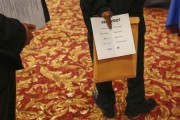 A man holds a pamphlet handed out by a recruiter while attending a job fair in New York, June 11, 2013.