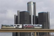 Two cars of the 'people mover' public rail are seen covered with a advertisement for the 2014 Chevy Silverado pickup truck as they move past General Motors World Headquarters in Detroit, Michigan Janu